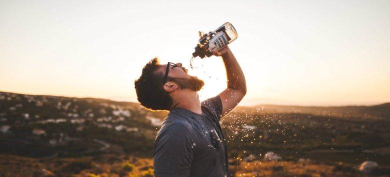 Photo d'un homme qui boit à la gourde, illustrant le fait de boire de l'eau après une consultation en ostéopathie.