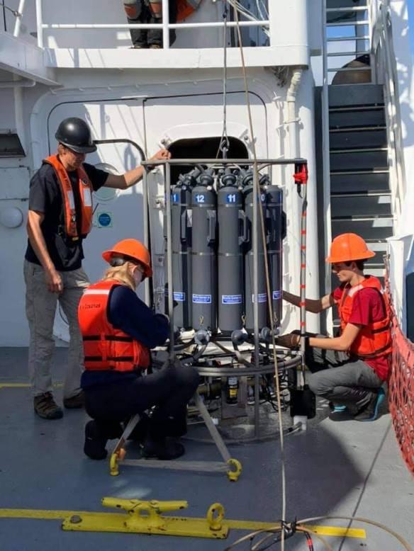 Three people prepare the CTD instrument on deck