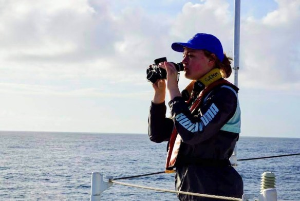 female with binoculars looks out to sea
