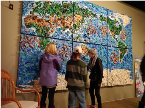three students examine a wall mural showing ocean gyres