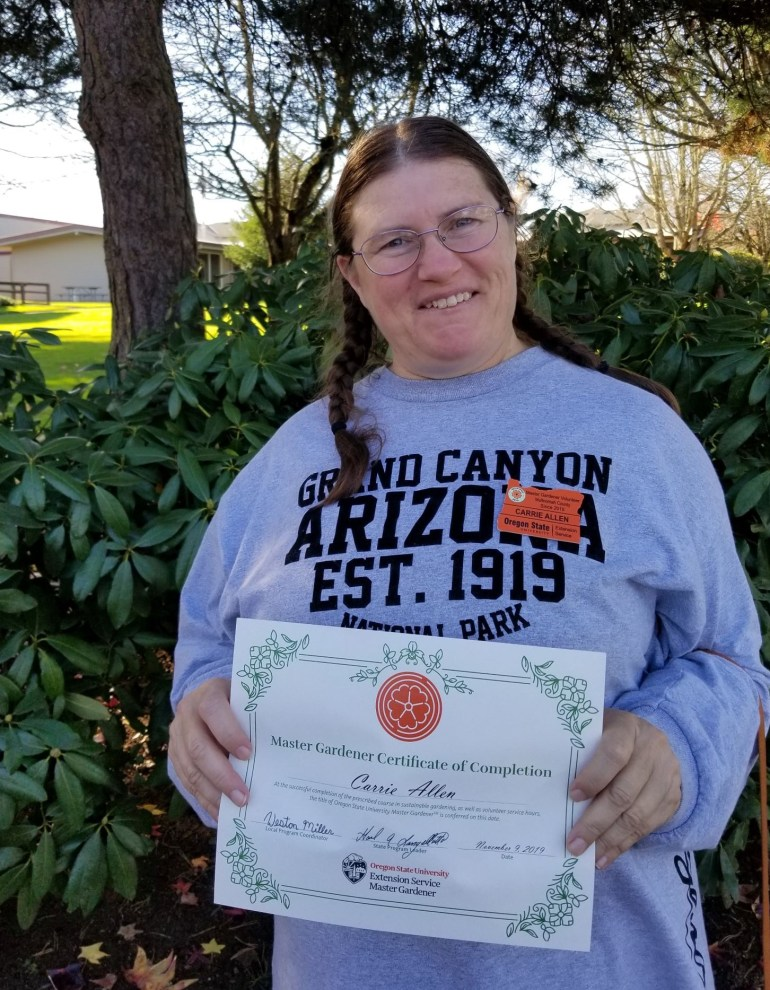 Carrie Allen smiles and holds her Master gardener Certificate of Completion and is wearing her OSU Master Gardener badge.