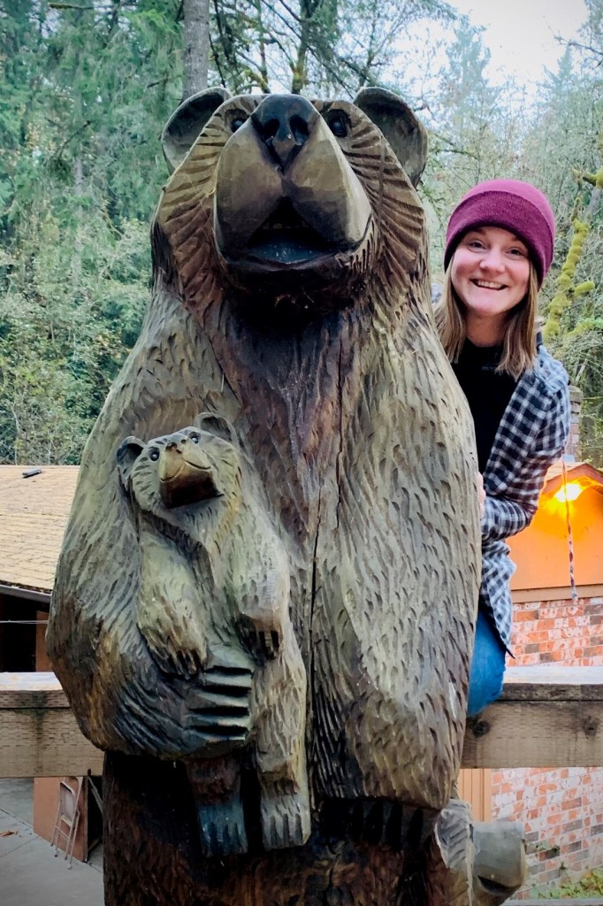 Janet Hohman peeks around wooden bear sculpture.