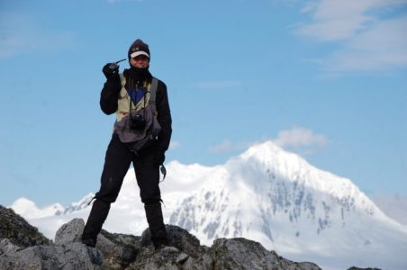 Birder teammate Kirstie Yeager listens for a call on the radio with Mt. Agamemnon behind her