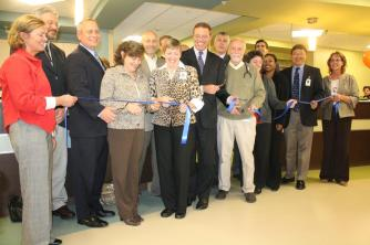 A group of dignitaries cuts the ribbon to mark the opening of the new Fulton Urgent Care.