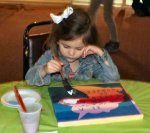 A young artist carefully ponders her next brush stroke