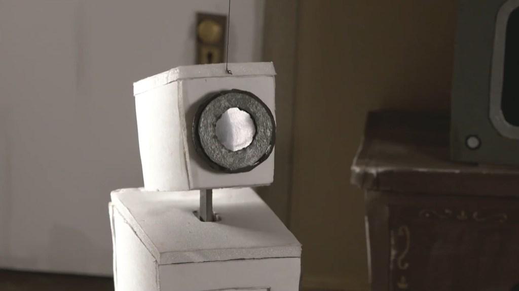 """Close do """"rosto"""" do robô olhando para o protagonista que o vê (ao robô) em primeira pessoa."""