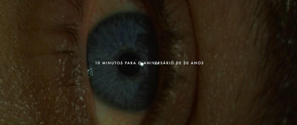 """Close de um olho azul visto de lado. Sobre a cena está escrito em branco e em caixa alta: """"10 minutos para o aniversário de 30 anos."""