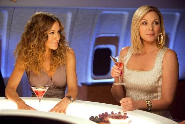 Duas mulheres loiras sentadas em um bar de avião bebendo coquetéis em Sex and the City