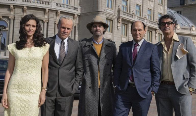 Uma mulher e quatro homens con trajes da decada de 70 pousam para foto - Otageek