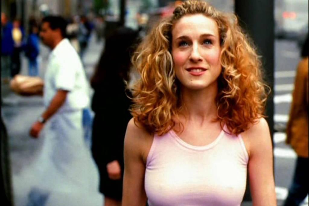 Mulher loira andando por Nova Iorque com um top rosa e sorrindo em Sex and the City