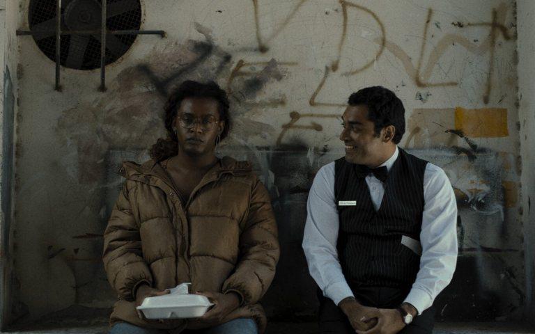 Manhãs de Setembro: casal sentado conversando encostados em um muro sujo