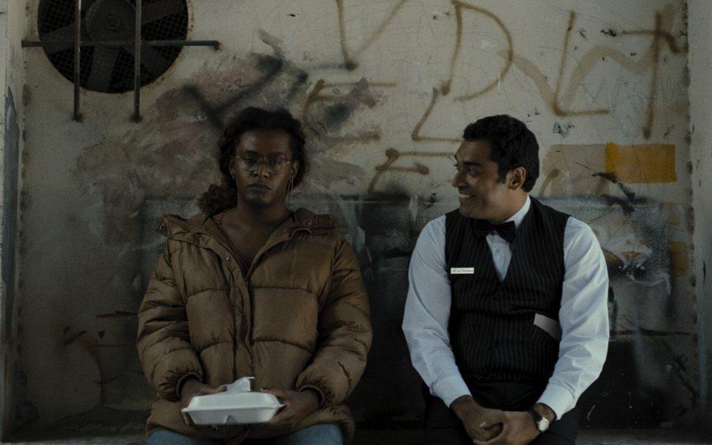 Um casal sentado conversando com uma marmita na mão encostados em um muro sujo