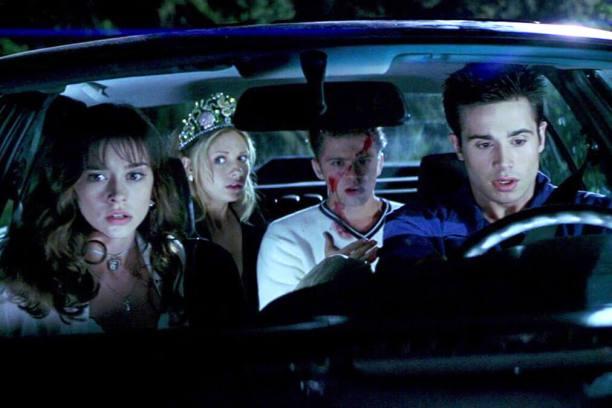 Duas meninas, uma loira e outra morena, e dois rapazes, um loiro com rosto sujo de sangue e outro moreno assustado, em um carro