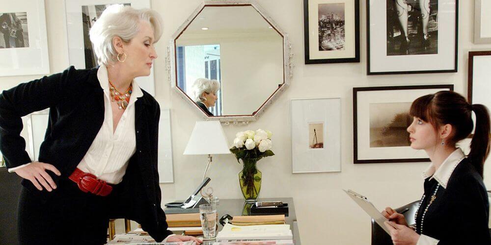 A imagem mostra a personagem Miranda falando uma lista de obrigações para a assistente Andy.