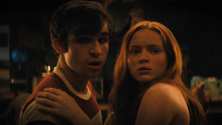 Um jovem moreno e uma jovem ruiva abraçados e assustados
