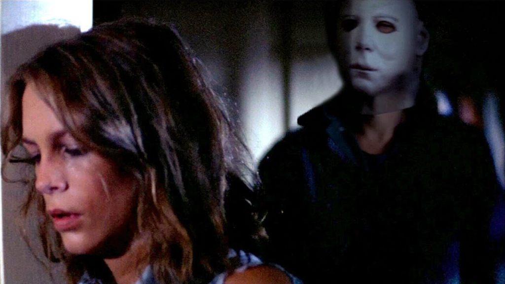 Mulher apoiada na porta enquanto um homem mascarado anda atrás dela nesse terror