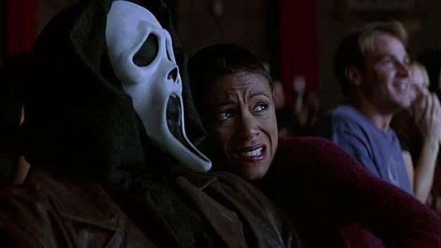 Moça careca assustada no colo de um homem com máscara de fantasma em um cinema