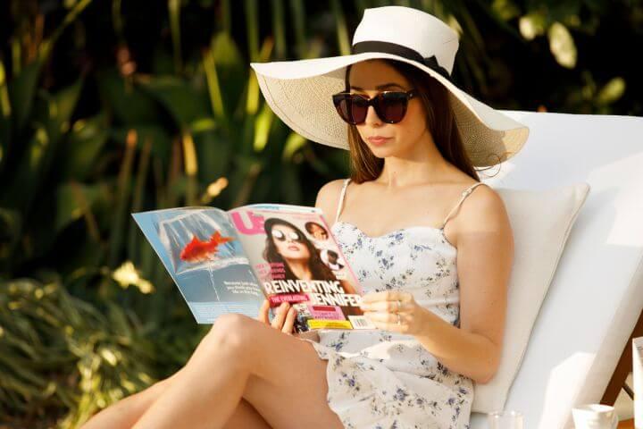 Mulher morena sentando enquanto lê uma revista