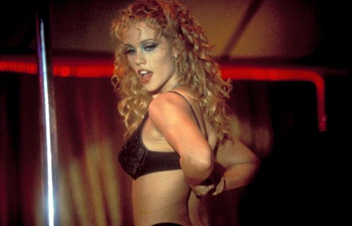 Mulher loira usando maquiagem enquanto dança seminua numa boate de streap