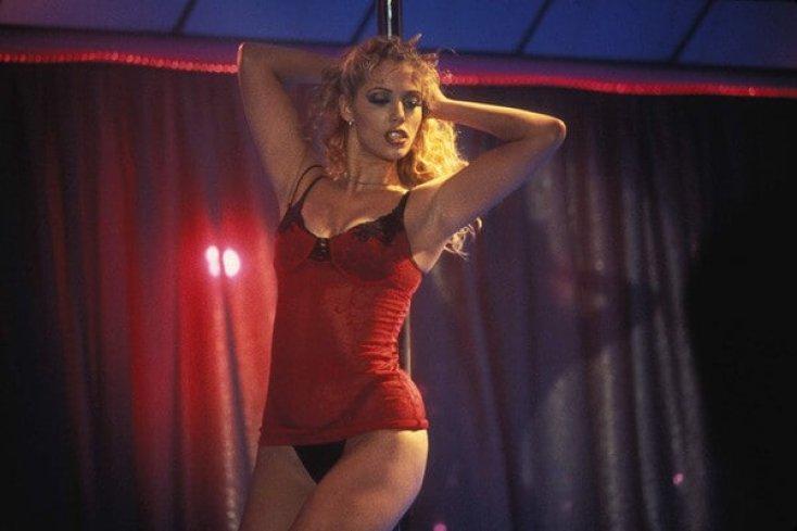 Mulher usando um vestido vermelho fazendo um pole dance