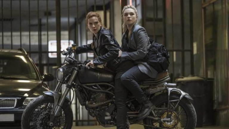 Uma mulher ruiva e uma loira sentadas em uma moto