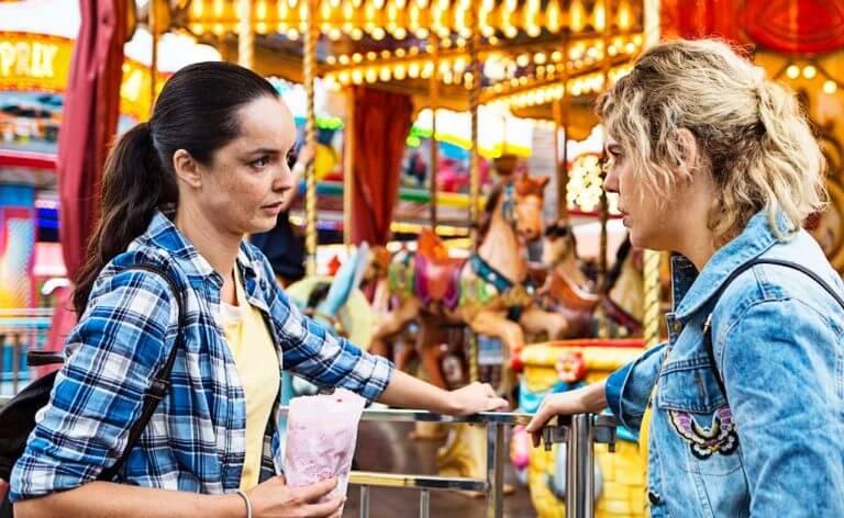Uma mulher morena e uma mulher loira conversando em um parque