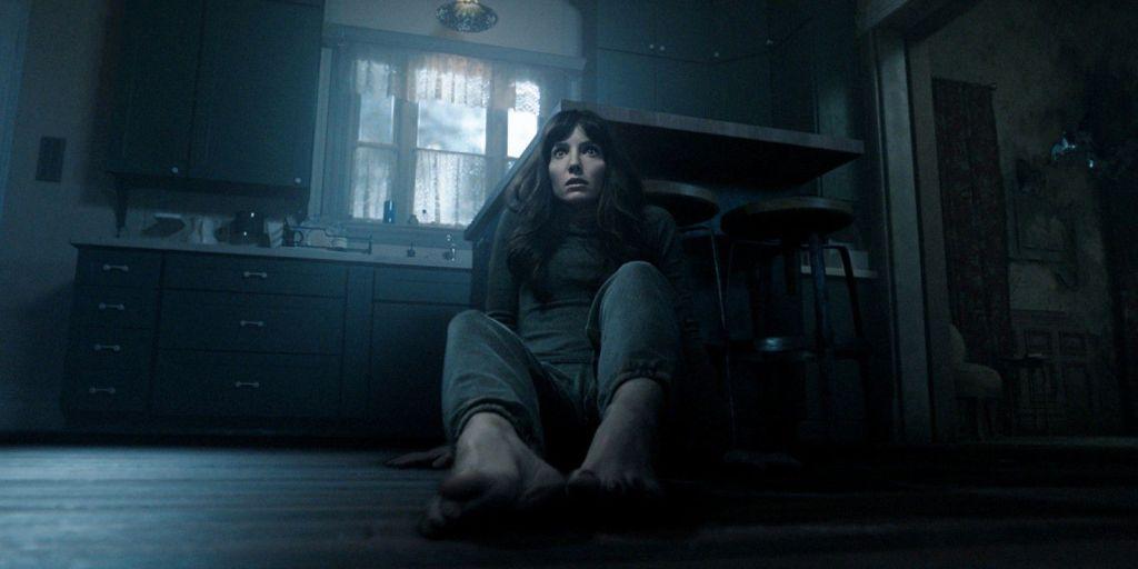 Madison sentada no chão escuro de sua casa em Maligno