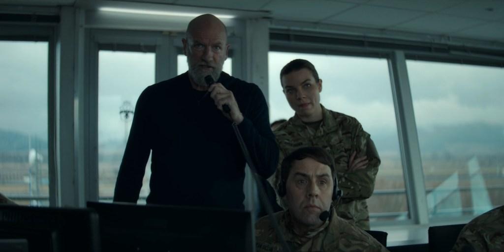 Soldados das forças especiais, na cabine de controle de voo do aeroporto falam para o avião, pedindo que os terroristas se entreguem.