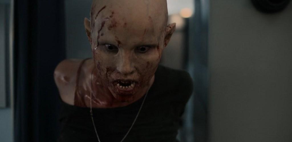 Nadja em sua transformação completa, com o rosto coberto de sangue (que não é seu), contempla, com olhar vidrado, para alguma coisa no chão.