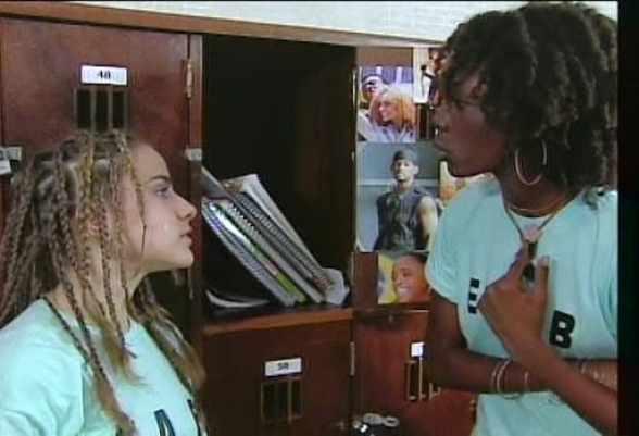 Um armário escolar de fundo com livros em dos armarinhos, duas meninas uniformizadas e aparentam estarem discutindo