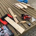 小屋と薪棚の建築端材で看板を作る準備をする