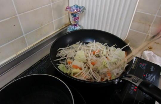 フライパンでカットした野菜を炒めている画像