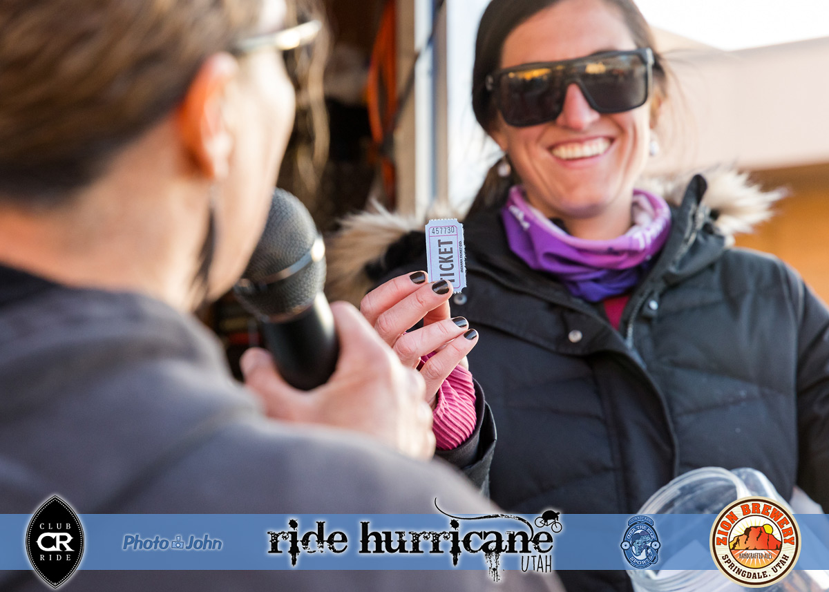 A smiling woman in sunglasses holding a raffle ticket