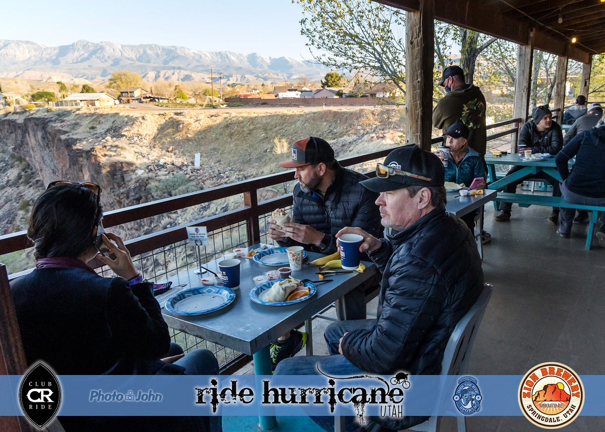 People eating breakfast on a deck in the morning with mountains in distance.