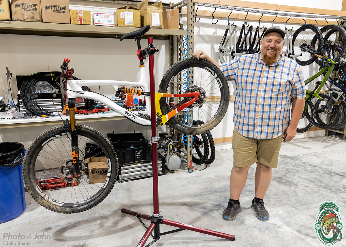 A man standing with a custom painted white, yellow and red full suspension mountain bike in a bike stand, in a warehouse.