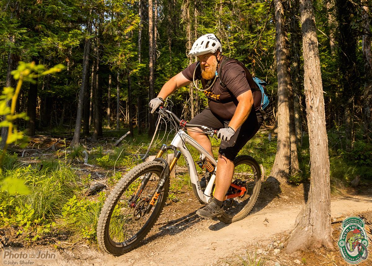 Mountain biker cornering hard in the forest on a white, mixed-wheel, full-suspension mounrain bike.