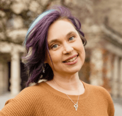 Photo of Kim Ashbourne smiling with brown shoulder-length hair with purple and blue streaks and a brown sweater in front of a columned building