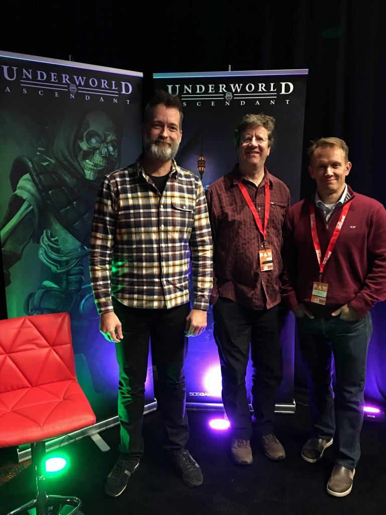Joe, Paul, and Walter standing in front of two Underworld Ascendant banners at PaxSouth