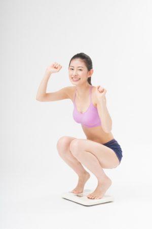 体重計の上で喜ぶ女性