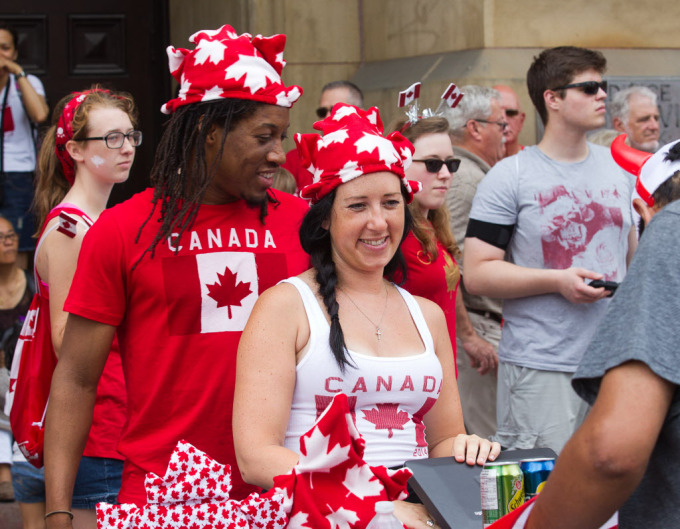 Jamal Carrington and Jill Cook sell soft drinks on Wellington Street as people flock to Parliament Hill and the downtown core to enjoy Canada's 147th birthday. Photo taken at 11:58 on July 1, 2014. (Photo by Wayne Cuddington / Ottawa Citizen)