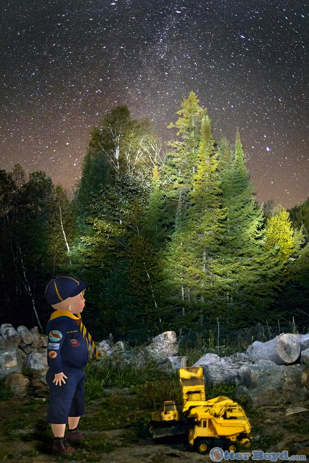 Boyd Scout in cub uniform playing with toy trucks under the chocolate milky way stars