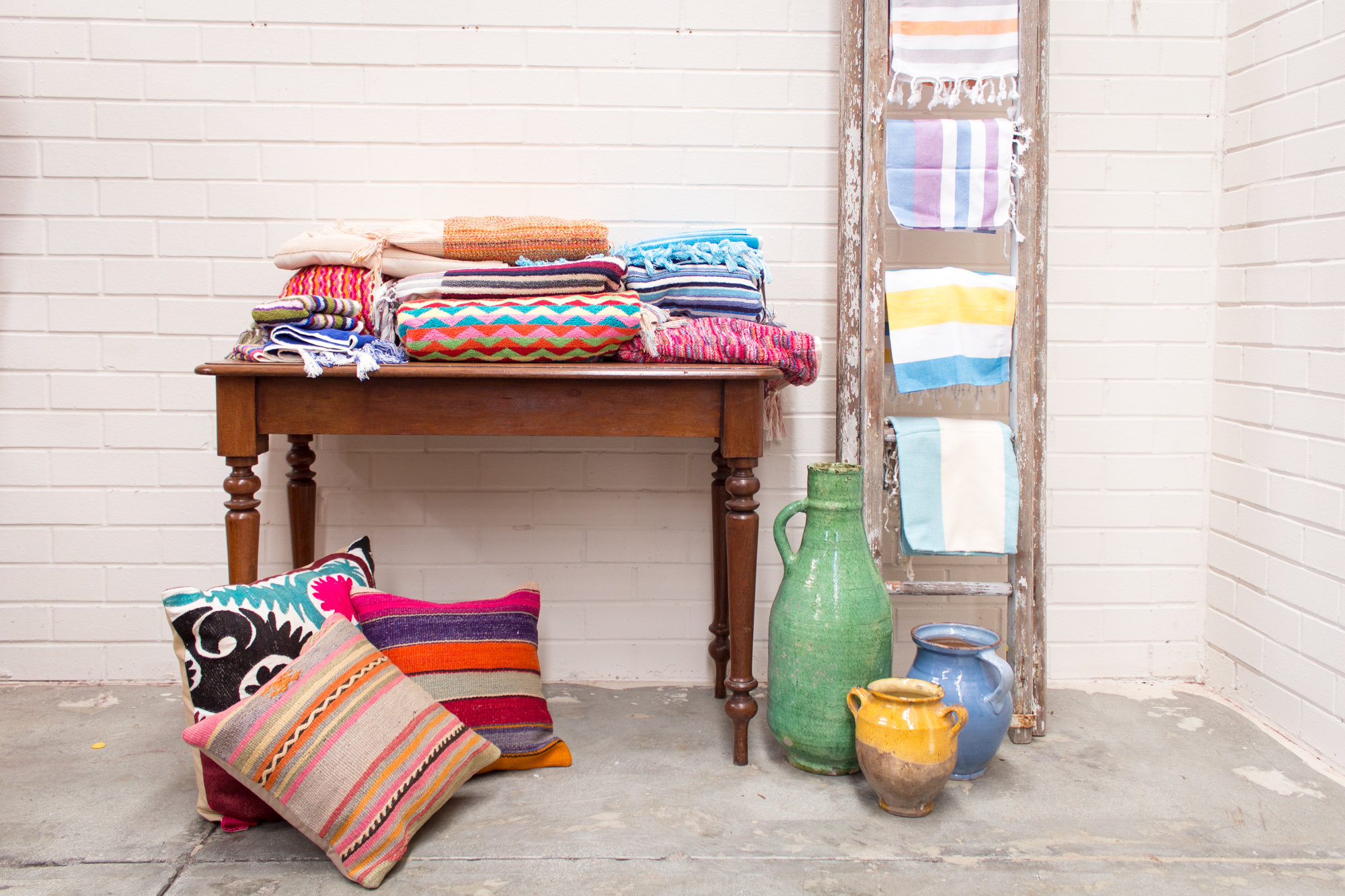 A Display of Kilim and Suzani cushions along with Turkish organic hand loomed towels and Bright colored pestemels