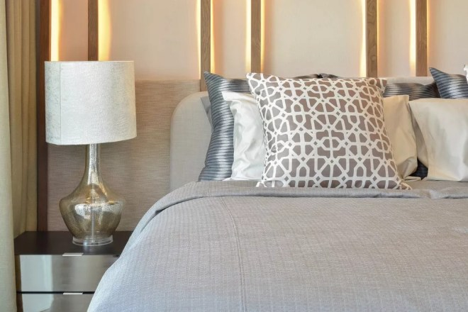 a cozy bedroom with the bedside lamp in focus