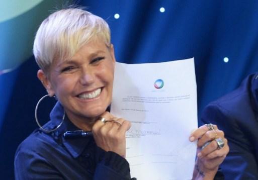 Xuxa exibindo seu contrato com a Record (Foto: Divulgação)