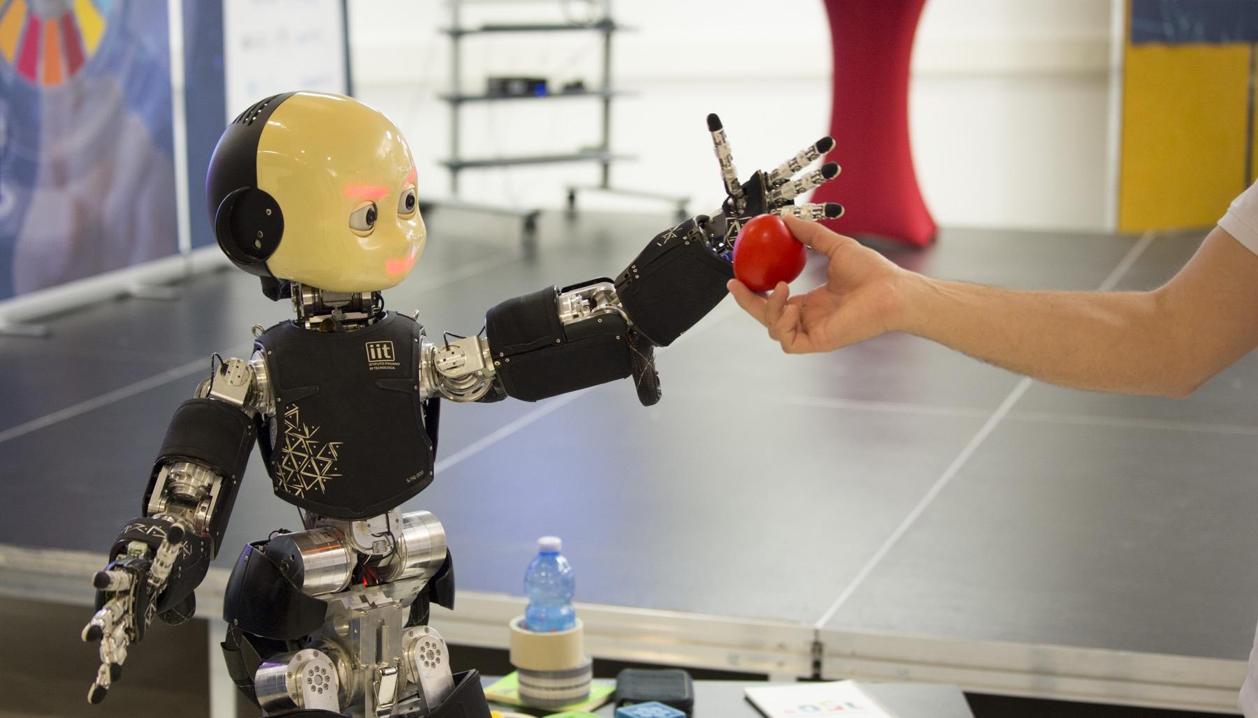 Robot sięgający po jabłko z ręki człowieka