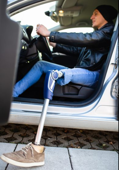 Young,Man,With,Prosthetic,Leg,Driving,Car.,Selective,Focus.