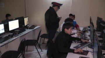 Сотрудник Енбекшинского РОВД проверяет документы посетителей компьютерного клуба