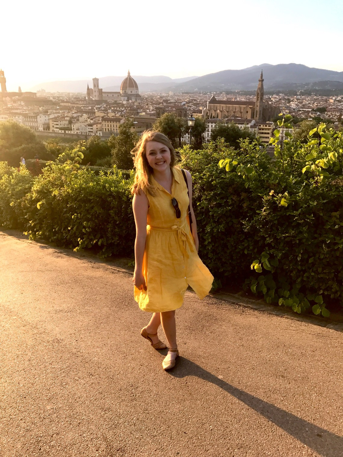 Bonnie walking to Piazza Michelangelo in yellow shirtdress with Florence skyline behind her