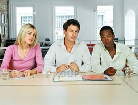 A woman and two men on an interview panel looking serious