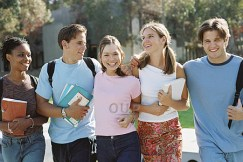 Group of teenagers walking in the sun holding books